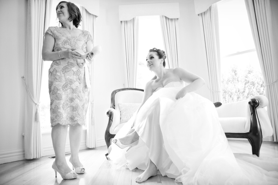 mother of the bride helping bride get ready at Greek wedding in
